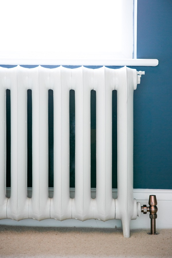 Duchess cast iron radiator painted in Farrow and Balls Wevet against a backdrop of Stiffkey Blue